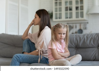 Sulking daughter dissatisfied mother sitting on couch looking different sides, family conflicts, misunderstanding and generational gap, older and younger female do not understand each other concept