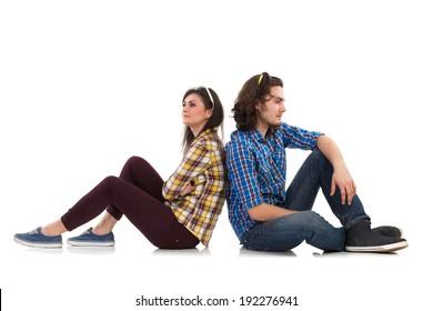 Sullen couple sitting on the floor back to back. Full length studio shot isolated on white.