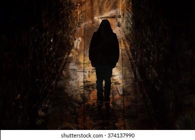 Sullen hooded boy in an underground tunnel