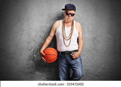 Sullen senior rapper holding a basketball and leaning against a rusty gray wall