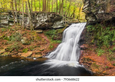 Sullivan Falls, a beautiful Pennsylvania waterfall, splashes down a cliff in an autumn landscape.