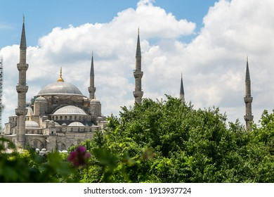 Sultan Ahmet (Blue Mosque) buried in greenery in summer, Istanbul, Turkey. Turkish islamic landmark with six minarets, main attraction of the city. View of the mosque with cloudy sky and green trees