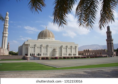 Sultan Qaboos Grand Mosque, Muscat, Oman during the afternoon in the blue sky and clouds and mountains in view.