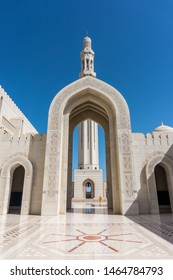 Sultan Qaboos Grand Mosque in Muscat, Oman. White marble floor, big arch and minaret in front.