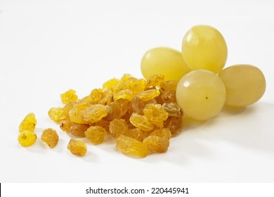 Sultana raisins and grapes on white background