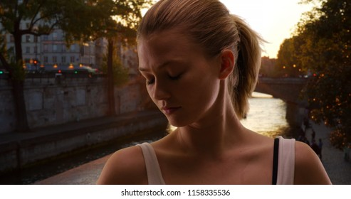 Sultry blonde female in Paris with eyes closed as the sun sets