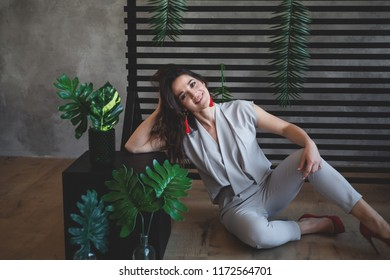 Sultry girl. Business portrait. Tropical decoration. Green leaves. Business style.  The girl is sitting on the floor. Cuban motives. stylish clothes
