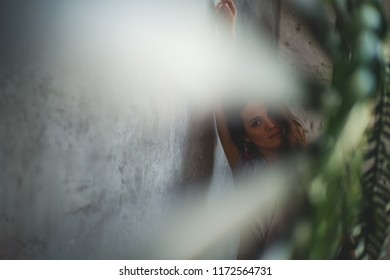 Sultry girl. Business portrait. Tropical decoration. Green leaves. girl behind bars, fencing. A dark room