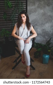 Sultry girl. Business portrait. Tropical decoration. Green leaves. business woman sitting in a chair.