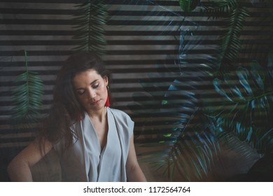 Sultry girl. Business portrait. Tropical decoration. Green leaves. double exposure. Mistaken thoughts. The girl in the smoky room.