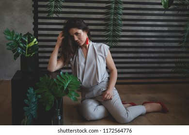 Sultry girl. Business portrait. Tropical decoration. Green leaves. Business style.  The girl is sitting on the floor