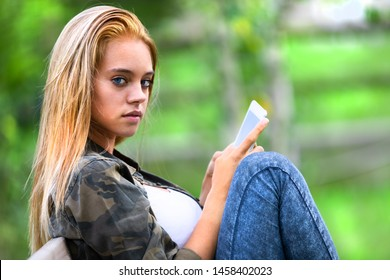 Sultry serious young woman looking aside at the camera as she sits outdoors on a garden bench using her tablet-pc