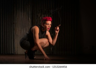 Sultry woman with fuchsia hair crouching and holding a cigar