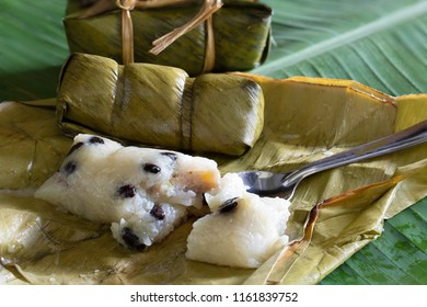 Suman, sticky rice stuffed with bananas, thai dessert on green banana leaf / Select focus