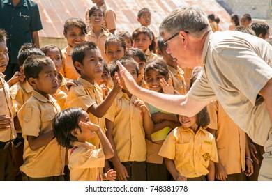 "Sumba, Indonesia - 9/13/2012: An American tourist gives a ""high five"" to a school boy at rural school near Waitabula."