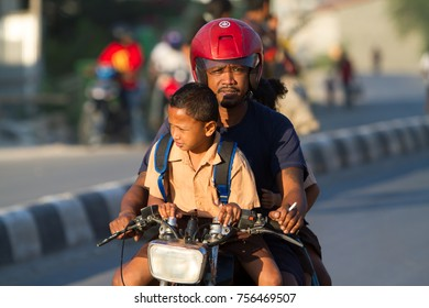 Sumba, Indonesia - 9/14/2012: father and son riding on a motercycle, he is taking his son to school.