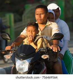 Sumba, Indonesia - 9/14/2012: a sumbanese family riding on a motercycle, father, mother, son and daughter.  Father is taking the children to school. Children are in school uniforms.