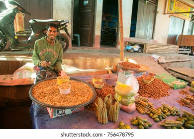 Sumba, Indonesia - 9/14/2012:  A Sumbanese man selling beans and vegetables  in an open air market on the island of Sumba in the village of Waitabula.