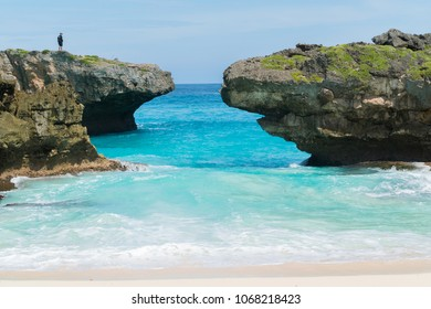 SUMBA, INDONESIA - MARCH 24, 2018: Tourist standing at the cliff of Beautiful nature  blue sea sand and white waves at Pantai Mandorak, Sumba, Indonesia