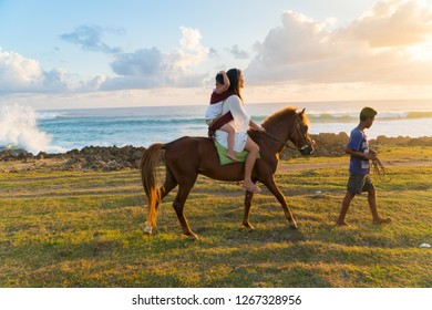 SUMBA, INDONESIA - MARCH 24, 2018: Tourist riding a horse during sunset at Pantai Pero, Sumba Island, Indonesia