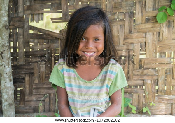 SUMBA, INDONESIA - MARCH 24, 2018: Little ethnic Sumbanese kids smiling and looking at the camera