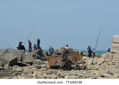 SUMGAIT, AZERBAIJAN - MAY 2 2014 Men fishing off rocks in Sumgait, Azerbaijan. A large group of men fish in the Caspian Sea.  This location was previously considered one of the most polluted