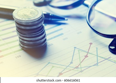 Summary report and financial analyzing concept, Pen and notebook with thailand coin and eyeglasses on paper report.