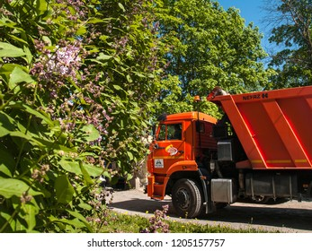 Summer of 2018 in the city of St. Petersburg:  KAMAZ truck of orange color among green trees in the