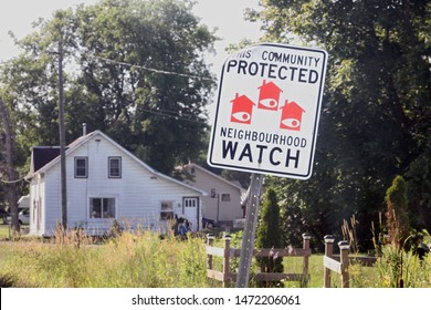 Summer 2019 photo of a country home  with a protected watch sign in front   near Lyn Ontario, Canada.