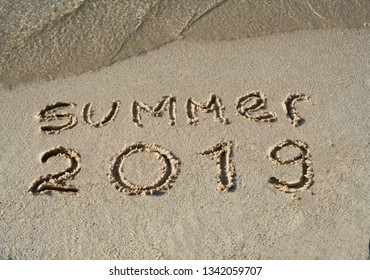 Summer 2019 written on sand of tropical beach