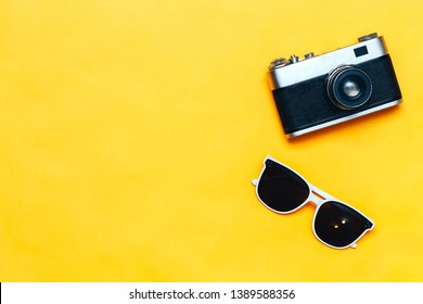 Summer accessories concept on yellow background, flatlay, copyspace, vintage camera, white sunglasses and swimsuit.