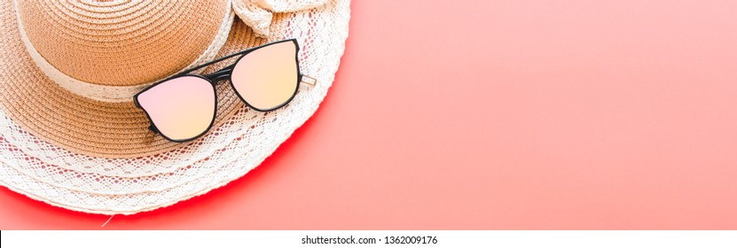 Summer accessories concept from sunglasses and straw hat, flat lay on red background pastel color for Advertising sale products and Website where you place banner ads.