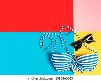 summer accessories and minimal flat lay concept from bikini, cloth and vacation item decorate on pastel and colorful background