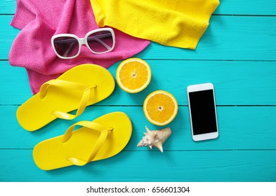 Summer accessories on blue wooden background. Yellow flip flops, towels, sunglasses, mobile phone and oranges. Mock up and top view, picturesque