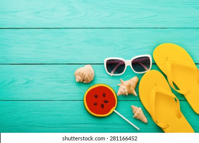Summer accessories and shells with candy on blue wooden background.