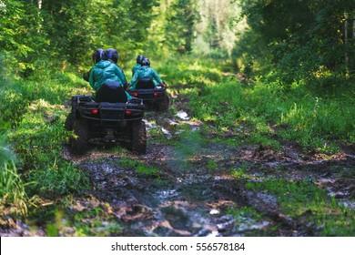 Sommerliche Aktivitäten für Erwachsene - eine Reise quad bikes die Straße. Mann auf ATV im Schlamm auf der Straße, um am Rennen über raues Gelände im Wald zu nehmen einen heißen Sommertag.