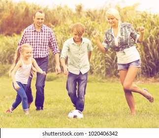 Summer activity at the lawn - happy family kicking the ball and laughing