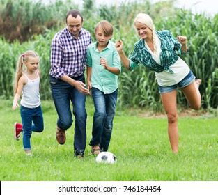 Summer activity - positive married couple with young children playing ball in the country home
