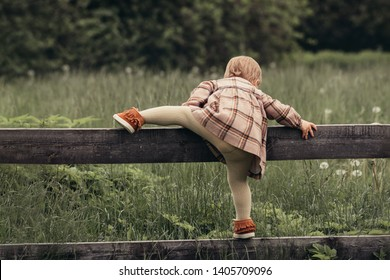 Summer adventures. Little girl climbs over the fence in the garden