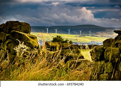 Summer afternoon on countryside, Stone wall on a farm with background bright moody blue clouds and wind turbines over hills in Lancashire, England UK