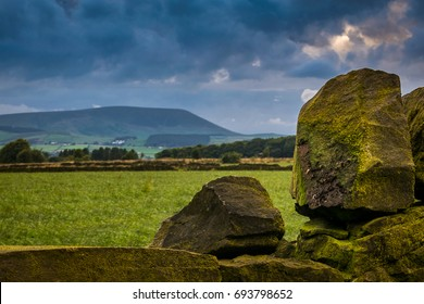 Summer afternoon on countryside, Stone wall with distance Pendle Hill, Clouds over a farm and hills in Lancashire, England UK