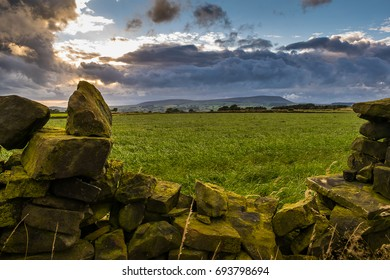 Summer afternoon on countryside, Stone wall on a farm in distance Pendle Hill, Clouds over hills in Lancashire, England UK