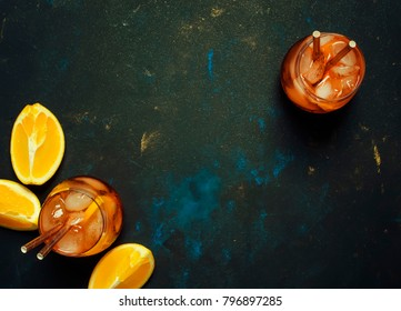 Summer alcoholic cocktail with bitter, sparkling wine, soda, orange and ice, dark background, top view