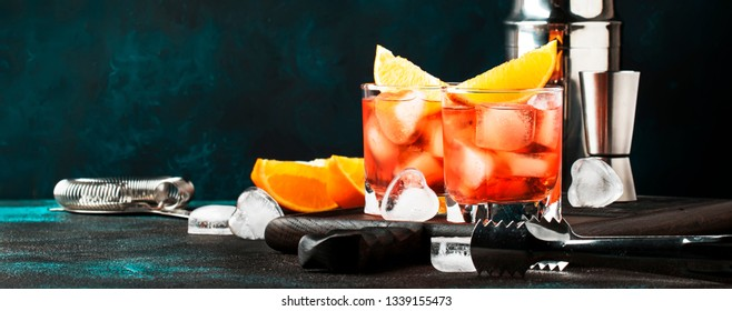 Summer alcoholic cocktail Negroni with dry gin, red vermouth and red bitter, orange slice and ice cubes. Brown bar counter background, bar tools, place for text, selective focus banner