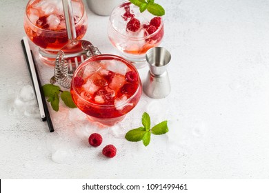 summer alcoholic drink with raspberry liqueur, ice and leaves of fresh mint on the table. bar accessories.
