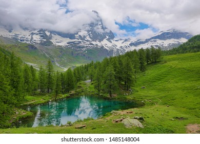 Summer alpine landscape with Matterhorn peak between the clouds on the Blue Lake (Lago Blu) near Breuil-Cervinia, Aosta Valley, northern Italy