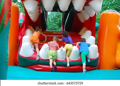 In the summer, in the amusement park, inflatable slide for kids climbs.