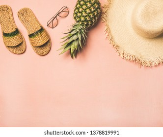 Summer apparel items. Flat-lay of summer flip flops, sunglasses, straw sunhat€ and fresh pineapple over pastel pink background, top view, copy space. Summer beach vacation concept