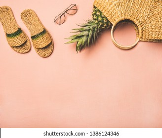Summer apparel items. Flat-lay of summer flip flops, sunglasses, wicker bag and fresh pineapple over pastel pink background, top view, copy space. Summer beach vacation concept