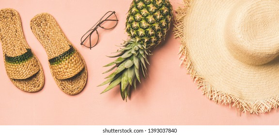 Summer apparel items. Flat-lay of summer flip flops, sunglasses, straw sunhat? and fresh pineapple over pastel pink background, top view, wide composition. Summer beach vacation concept